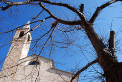Old stone church and bare tree Stock Photo