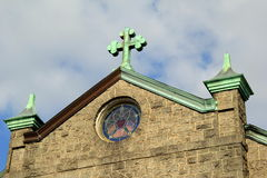Old stone church with copper cross atop it Stock Image