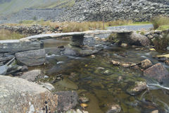 Old stone clapper bridge over mountain stream. Royalty Free Stock Images