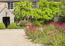 Old stone Cotswold cottage with courtyard flower garden Royalty Free Stock Photography
