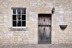 Old Stone Cottage. Architectural Detail of a Wooden Front Door and Sash Window of an Old Stone Home Stock Photo