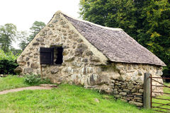 Old stone cottage. With slate roof and wooden shutter in rural setting Stock Photos
