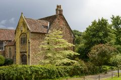 Old stone cottage among trees, Wells. View of ancient stone building surrounded by trees,  shot in bright light under a cloudy sky Stock Images
