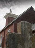 Old stone cross and brick church building on cloudy day Royalty Free Stock Images