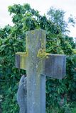 Old stone cross. In a church graveyard with moss on it Royalty Free Stock Photography