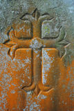 Old stone cross engraving. Old grunge cross engraving with lichin growing on it Royalty Free Stock Photo