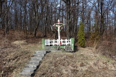 Stone cross in forest with dead trees and grass. Old stone cross with candles in front of it located in forest with dead trees and brown grass and concrete steps Royalty Free Stock Photography