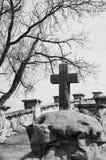 Old stone cross sitting on rock. Stock Photos