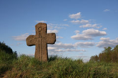 Old stone cross with sword symbol. Standing in green grass Royalty Free Stock Photo