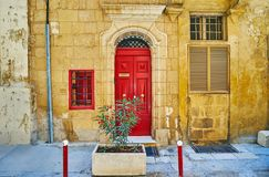 The red door, Valletta, Malta. The old stone edifice decorated with wooden bright red door with relief doorframe, St Ursula street, Valletta, Malta Royalty Free Stock Photos