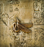 Egyptian hieroglyphs. Old stone with Egyptian hieroglyphs and symbols. Relief antique texture in Egypt. Winged god of Egyptian mythology, amid ancient Royalty Free Stock Photography