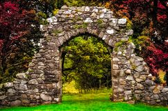 Old stone entrance wall in the garden with colorful foliage. Old stone entrance wall in the garden with beautiful colorful foliage stock photo