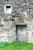 Old stone facade with a door and window Royalty Free Stock Image