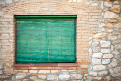 Old stone facade with green wooden shutters in the window Stock Photos