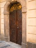 Old stone facade made of carved stone and vintage wooden door in a majestic house Stock Images