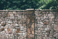 Old stone fence and green deciduous plants behind Stock Photo