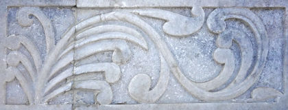 Old Stone Flourish Carving. An image of a unique stone carving of a flourish spiraling plant in marble. This was a temple design embellishment royalty free stock photos