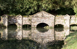 Old stone footbridge reflected in river. Historic carved stone footbridge across a river on the Stowe estate in Buckinghamshire England stock images