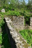 Old stone foundation of ruined building. Craggy textured stone wall on a sunny spring day stock photo