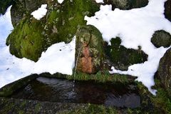 Old stone fountain with human shape and face. Stone covered with snow, grass and moss. Piornedo, Lugo, Spain. stock photos
