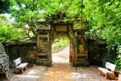 Old stone gate leading into enigmatic tropical garden Royalty Free Stock Images