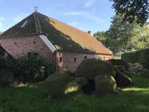 Old stone grave dolmen next to a house stock photography