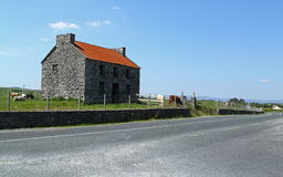 Old stone house. An old stone house with cows near a road stock photo