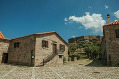 Old stone house on cobblestone alley and castle wall. Facade of old stone house on cobblestone alley and castle wall on top of hill at Linhares da Beira. A stock photos