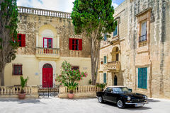 Old stone house with colorful windows and black classic style convertible car - Mdina, Malta Stock Image