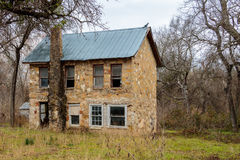 Old Stone House. Old deserted stone two story house with a tin roof. Some broken glass windows and old fireplace Royalty Free Stock Photo