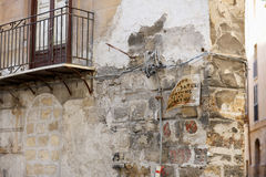 Old stone house. Detail of the corner of an old stone house with wiring and oldness of signboard in Palermo, Italy. Text: `Welding work Electric and gas welding Stock Photo