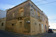 An old stone house in Mellieha, Malta. Mellieha, Malta – January 27, 2016. Residential house of Maltese stone with ironwork and stonework balconies, a lamp Stock Image