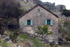 Old stone house in the mountains. With green Windows with fortress Royalty Free Stock Image