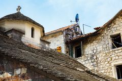 Old stone house in a poor neighborhood, standing next to a small ancient church. Historical architecture. Old Town of Budva, Montenegro Stock Photo