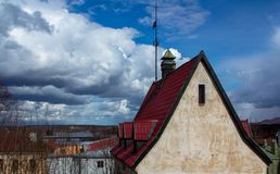 Old stone house with a red roof. On a cloudy sky background Stock Photo