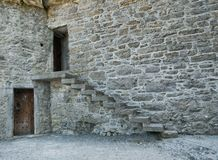 Old stone house with a staircase and two doors stock images