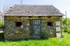 Old stone house. With a tiled roof, around the house growing dense green grass, horizontal photo Royalty Free Stock Photo