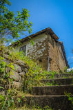 Old stone house with a tiled roof around the house growing dense green grass horizontal photo. An old house, a house of mud. East Serbia Stock Photos