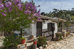 Old stone house and violet flowers in village of Aliki, Thassos island, Greece Royalty Free Stock Photo