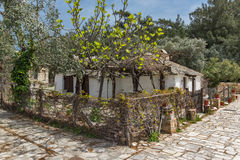 Old stone house and violet flowers in village of Aliki, Thassos island, Greece Stock Image