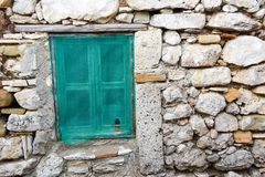 Old stone house and old windows. An opening in the wall or roof of a building or vehicle that is fitted with glass or other transparent material in a frame to Stock Photo