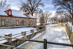Old stone house. Winter scene beside a canal with ice on a nice sunny day Stock Photography