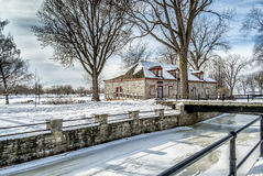 Old stone house. Winter scene beside a canal with ice on a nice sunny day Royalty Free Stock Images