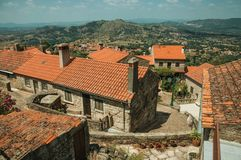 Old stone houses with alley making a curve in Monsanto. Old stone houses with big chimneys and deserted alley making a curve, over hilly landscape in a sunny day stock image