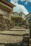 Old stone houses in cobblestone alley on slope with steps. Facade of old stone houses in cobblestone alley on slope with steps, in a sunny day at Alvoco da Serra stock images