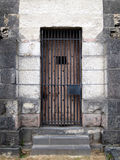 Old stone jail wooden door with iron bars. Old wooden door of stone jail with iron bars Royalty Free Stock Images