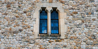 Old stone medieval wall with two windows in centre Stock Photos