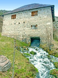 Old stone mill and powerful stream of water Stock Photos