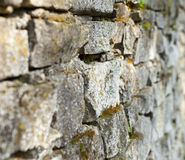 Old stone moss-grown masonry with rich texture Stock Images