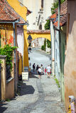 Old stone paved street with tourists from Sighisoara Stock Photography